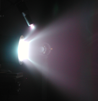 Figure 1: One of the space thrusters that is being studied at the Space Propulsion Laboratory at MIT firing. The bright exhaust is the plasma. Photo credit: Stephen Gildea.