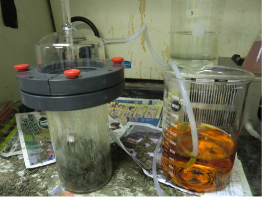 Figure 2: Ozonation reactor (left) including a soil sample, and the excess ozone gas is trapped in the beaker to the right to be measured.
